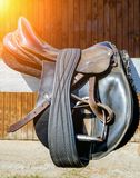 Leather Sun Saddles on fence. Leather Sun Saddles horse with stirrups on a back of fence royalty free stock photography