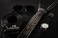 Leather, sunglasses, tie, cuff-links, watch on a black background. Leather belt with metal buckle, sunglasses, tie, cuff-links, watch with a leather strap on a royalty free stock images