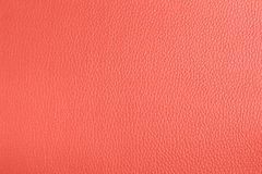 Leather textured background in living coral color. stock image