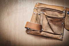 Leather tool belt for building tooling on wooden board Stock Image