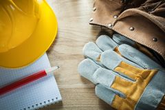 Leather tool belt protective gloves building helmet copybook pen Royalty Free Stock Photo