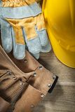 Leather tool belt protective gloves building helmet on wooden bo Royalty Free Stock Images