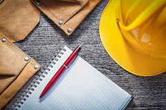 Leather tool belt protective hard hat checked notepad pen on woo Stock Image