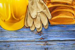 Leather tool belt safety gloves hard hat on blue wooden board.  royalty free stock image