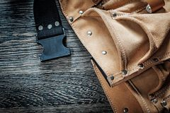 Leather toolbelt on black wooden board.  Stock Images