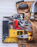 Leather toolbelt building implements on wood board construction. Concept Stock Photos