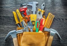 Leather toolbelt building tools on wooden board directly above.  Stock Images