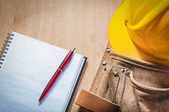 Leather toolbelt safety hard hat checked notepad pen on wood boa Royalty Free Stock Photography