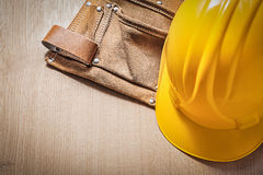 Leather toolbelt safety hard hat on wood board.  Stock Photography