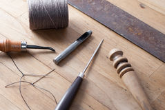 Leather tools for a craftsperson to make hierlooms. Various leatherworking tools in a pleasing arrangment on a wooden workbench stock images