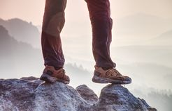 Leather trekking shoes on peak of rock above misty valley. Free way traveller stock image