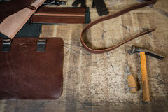 The leather for the unfinished messenger. With crafting tools on working desk with the scratches. Working process in the leather workshop. Grunge table. View royalty free stock images
