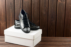 Leather upper metallic trandy womens shoes on brown wooden backg Stock Image