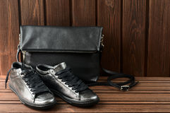 Leather upper metallic womens shoes and black leather bag on bro Stock Photos