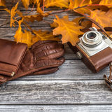 Leather wallet with gloves and camera on wooden background Royalty Free Stock Photo