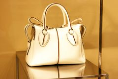 Leather white women bag on the storefront close-up, front view stock image