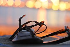 Leather woman sandal in sunset background. Leather woman sandal in a moody sunset background Stock Photo