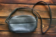 Leather women bag on wooden background.  royalty free stock photography