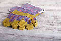 Leather work gloves lying on wooden board Stock Photos