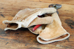 Leather Work Gloves and Pliers on Workbench Royalty Free Stock Photos