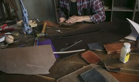 Leather worker man sitting behind table with tools and holds leather key case Stock Photos