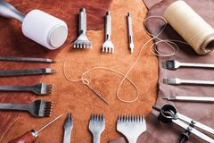 Leather-working tools on natural brown leather, in workshop Stock Photography