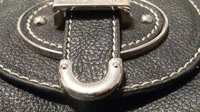 Leather Works. A close-up detailing the craftsmanship in the stitching and fixtures of a black leather purse Stock Photo