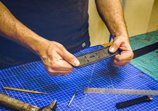Leather workshop master holds a black belt Royalty Free Stock Photography