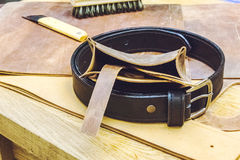 Leather workshop and tools with black belt close up Royalty Free Stock Images