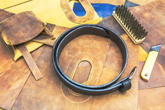 Leather workshop and tools with black belt Royalty Free Stock Photos