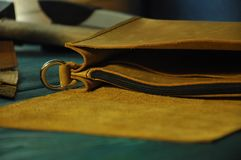 Leather workshop Yellow leather and tools on the table royalty free stock images