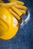Leather yellow protective gloves building helmet and claw hammer Stock Photo