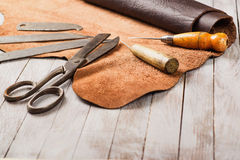 Leathersmith's work desk . Pieces of hide and leather working tools on a work table. Royalty Free Stock Images