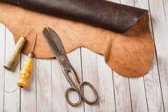 Leathersmiths arbetsskrivbord Stycken av funktionsdugliga hjälpmedel för skinn och för läder på en arbetstabell Arkivbild