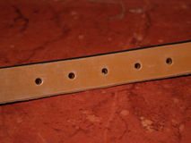 Leatherwork. Leather strap. London tan with holes Royalty Free Stock Photos