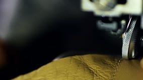 Leatherworker acaba de coser las piezas de cuero Ciérrese encima del trabajo de las manos del hombre almacen de video