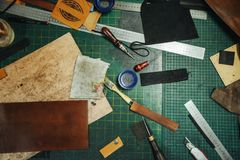 Leatherworking tools. Riveter, awl, ruler, pliers, tassels, pencil, leather pieces, rivets and fasteners are on the. Tools for leather processing. Riveter, awl stock photos