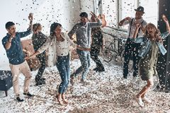 Leave all the worries behind! Full length top view of happy young people gesturing and smiling while dancing with confetti flying. Everywhere royalty free stock images