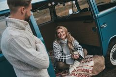Leave all your worries behind!. Beautiful young women looking at her boyfriend and smiling while sitting in blue retro style mini van Royalty Free Stock Photography
