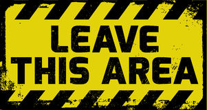 Leave this area sign. Yellow with stripes, road sign variation. Bright vivid sign with warning message Royalty Free Stock Photo
