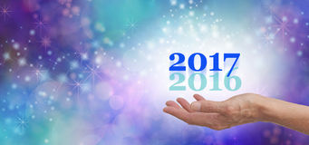 Leave 2016 behind for 2017. Female hand open palm outstretched with a pale green 2016 and a cobalt blue 2017 floating up on a white ball of light and blue green Stock Images