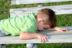 Leave Me Alone. Young boy laying face down on a park bench, trying to hide stock images