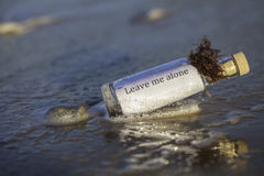 Leave Me Alone. Message in a bottle with the text 'leave me alone'. Many connotations relating to isolation and segregation from society etc Royalty Free Stock Image