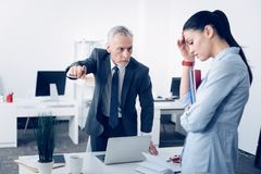 Mad chief dismissing delinquent female employee. Leave the office. Selective focus on an angry mature boss leaning on a table and fingering at a door while royalty free stock photos