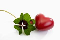 Leaved klaver vier, rood hart en onzelieveheersbeestje Stock Fotografie