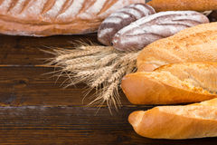 Leavened bread loaves with wheat stalks on table Royalty Free Stock Image