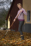 Leaves in autumn. Active pregnant woman sweeping autumn leaves in the garden royalty free stock photos