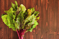 Leaves of beetroot on the wooden background. Leaves of beetroot on the brown wooden background Royalty Free Stock Image