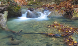 Leaves in blue water. Little waterfall in Crimea mountains in autumn Royalty Free Stock Photography