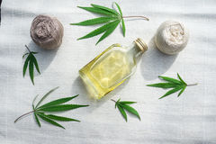 Leaves of cannabis, balls of yarn and bottle of hemp oil on canv Stock Photos